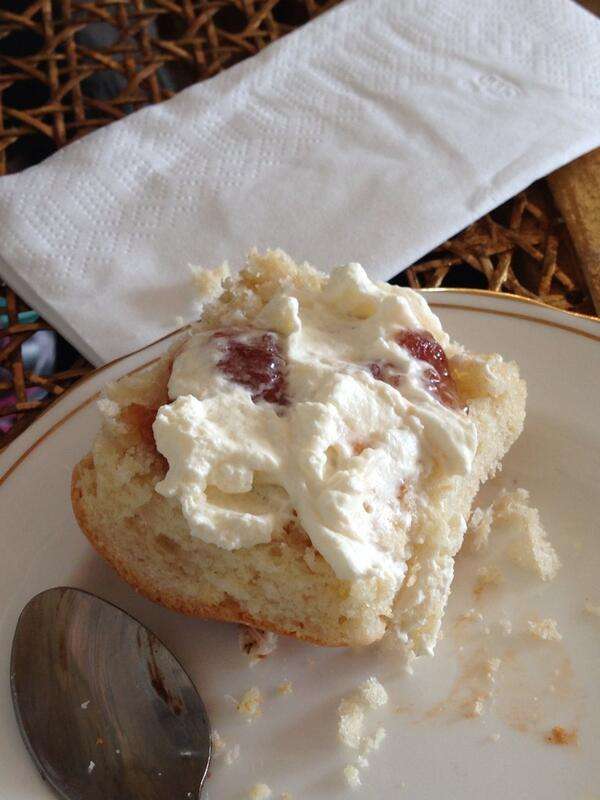 A scone with cream and jam, on a plate